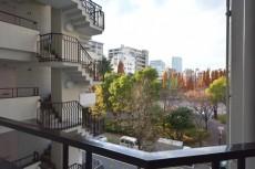 明石町アビタシオン 共用廊下からは公園の緑が見えます。